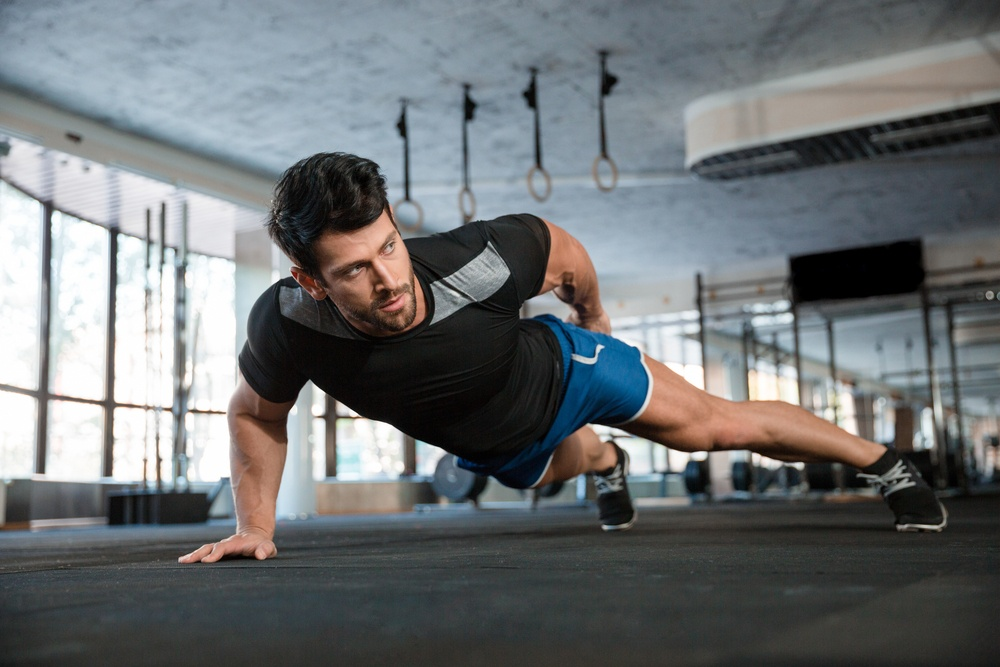 Portrait of a handsome man doing push ups exercise with one hand in fitness gym