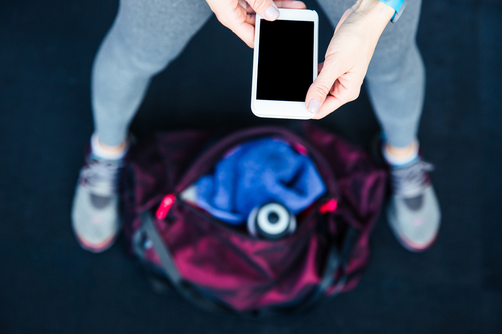 Closeup image of a sports woman holding smartphone